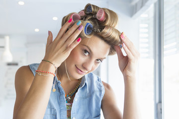 Portrait of smiling woman with curlers in hair at salon