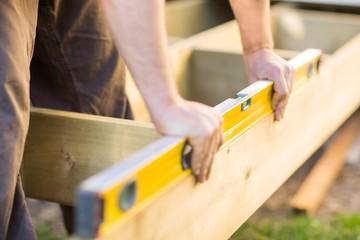 Fototapeta Carpenter's Hands Checking Level Of Wood At Site obraz