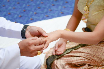 Groom wears a diamond ring onto the brides hand