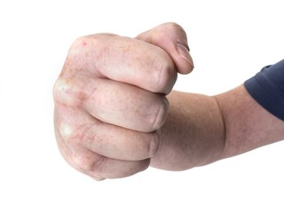 Close up photo of a large threatening fist isolated on white