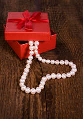 red gift box with a pearl necklace in the shape of heart