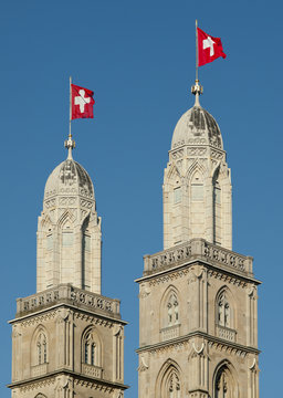 Zurich Grossmuenster cathedral with Swiss flags on 1-Aug