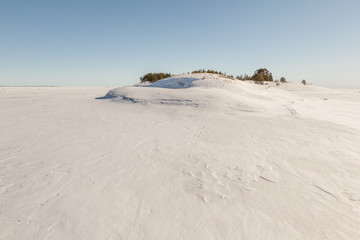 Winter, stony snow-covered island of Ladoga lake. A winter lands
