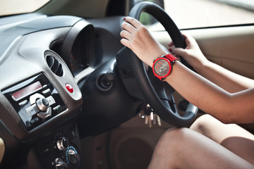 Close-up of a woman's hand on steering wheel in a modern car