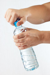 Female hands opening a bottle of mineral water