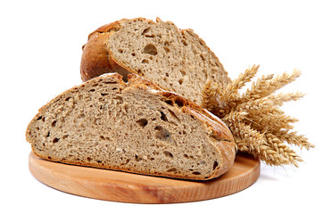 Two halves a loaf of rye bread and wheat ears.