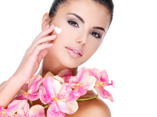 Wall Mural - woman applying cosmetic cream on face with pink flowers on body