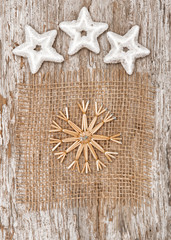 Straw snowflake with stars on textile and old wood