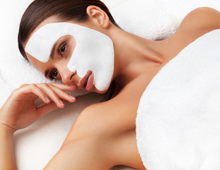 Wall Mural - Young woman at spa salon with cosmetic mask on face.