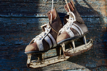 vintage pair of mens  ice skates hanging on a wooden wall with c