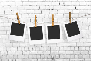 photos hanging on a clothesline on brick wall background