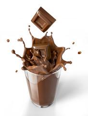 Chocolate cubes splashing into a chocolate milkshake glass.