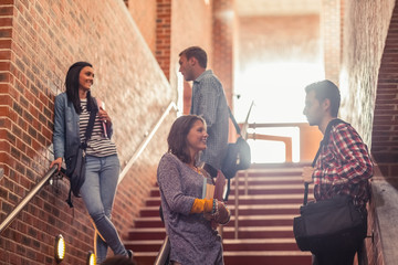 Casual students standing on stairs chatting