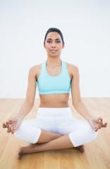Calm slim woman meditating in lotus position
