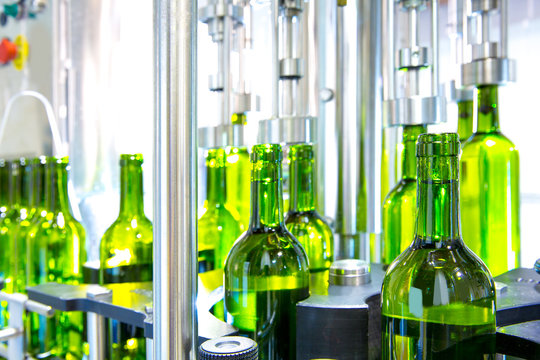 white wine in bottling machine at winery