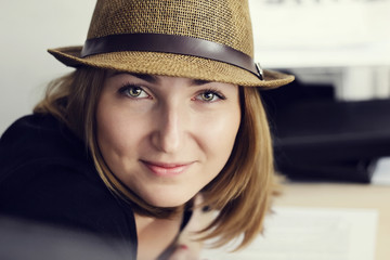 Closeup portrait of beautiful blonde girl in hat is smiling