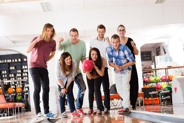 Woman Bowling While Friends Motivating in Club