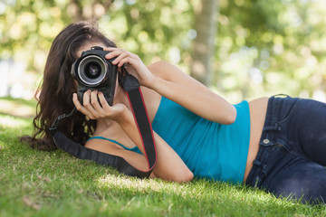 Front view of pretty brunette woman lying on a lawn taking a pic