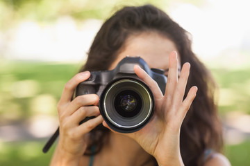 Front view of young brunette woman taking a picture