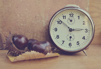 Vintage chestnut and clock on wooden background
