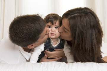 Mother and Father Kissing Daughter