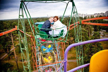 Newly married couple ridding in tycoon park on ferris wheel