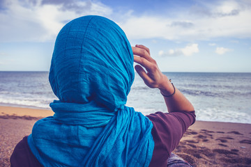 Rear view of woman with headscarf looking at the sea