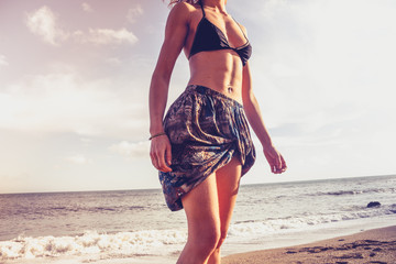 Young woman in colorful skirt walking on the beach