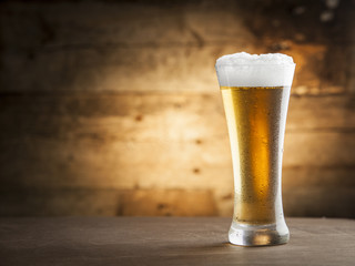 Glass of beer over a wooden background