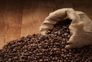 roasted coffee beans with cloth sack on wooden texture