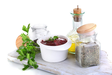 Raw liver in bowl with spices and condiments isolated on white