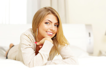 Young beautiful blonde woman lying on the bed at home