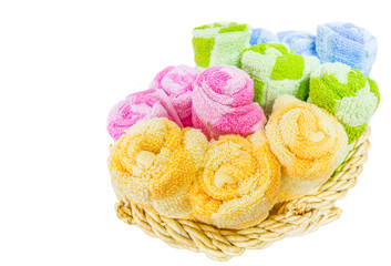 Rolls of different colors of towels in a wicker basket.