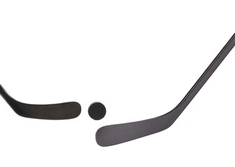 Two black ice hockey stick and puck.
