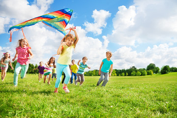 Cute group of kids run with kite
