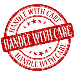 Handle with care grunge damaged red round stamp on white