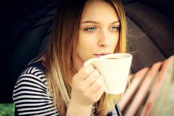 womanl drinks fragrant coffee with pleasure under umbrella