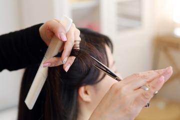 女性の毛先を切る