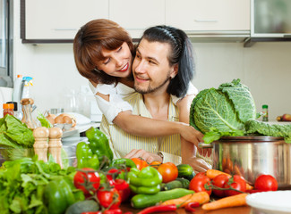 Loving couple cooking vegetables