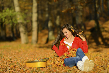 Beautiful brunette guitar player girl in the forest