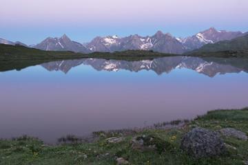 Mountain range mirroring in an alpine lake at sunrise