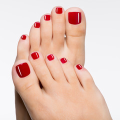 Foto op Plexiglas Pedicure Beautiful female feet with red pedicure