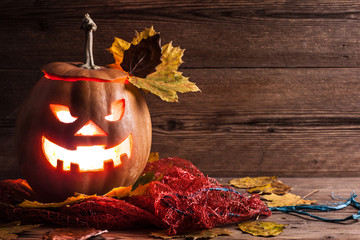jack-o-lantern with leaves on wooden background