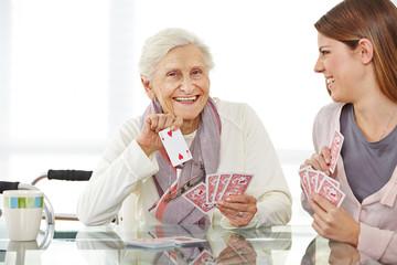 Wall Mural - Frau spielt mit Seniorin im Seniorenheim Karten