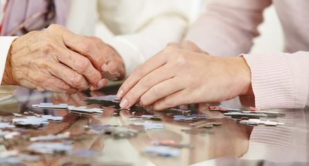 Wall Mural - Hände von Seniorin und Frau mit Puzzle