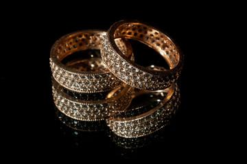 Wedding rings lie on a mirror