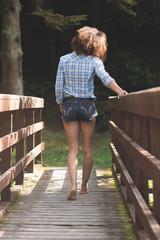 Rear view of gorgeous brunette walking on bridge