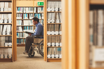 Man sitting in wheelchair looking at a book