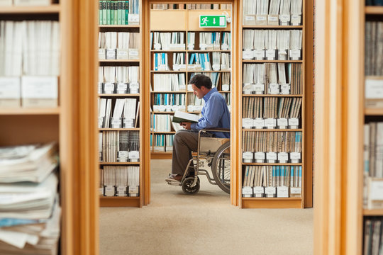 Man sitting in wheelchair reading a book