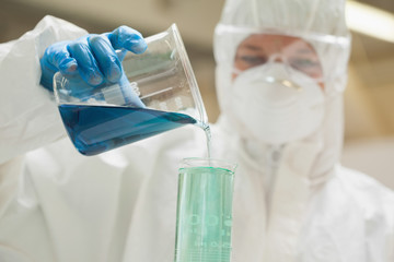 Lab assistant with mask mixing blue liquid in beaker